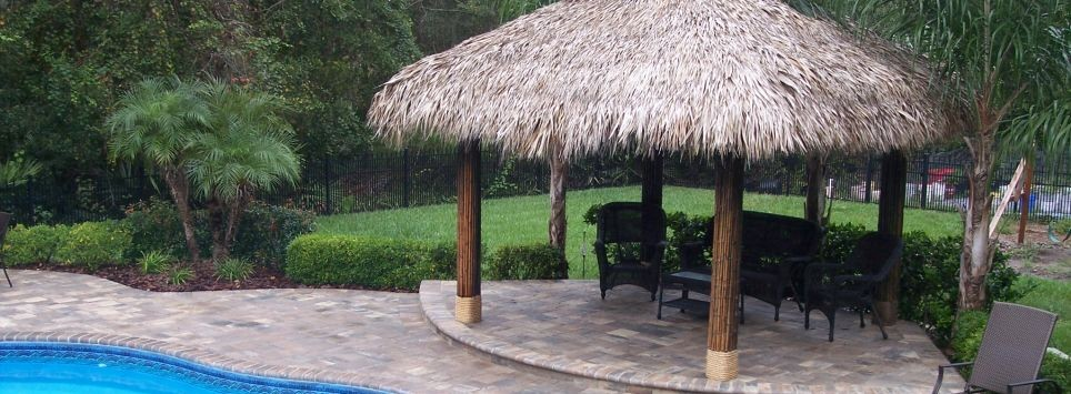 Tiki hut with natural thatch and bamboo wrapped poles