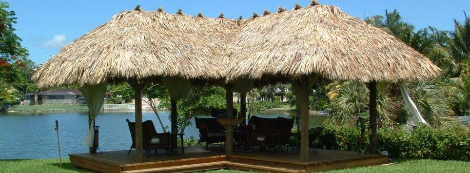 L shaped tiki hut with natural thatch and deck. Furniture underneath